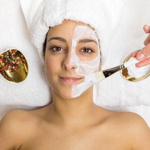 Retrato de una mujer joven, con una mascarilla aplicada en la mitad de la cara. A la derecha se ve la mano de una terapeuta aplicando la mascarilla con un pincel blanco.
