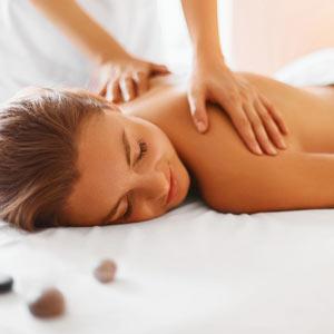 Foto a color de una mujer rubia recibiendo un masaje relajante. Se ven las manos de la terapeuta apoyada en su espalda