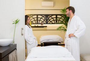 Foto a color de una pareja a punto de recibir un masaje en wellness boutique Experience. En el centro se ven 2 camillas preparadas con toallas blanca. la pareja esta de pies, mirándose y apoyados a cada lado de la pueta