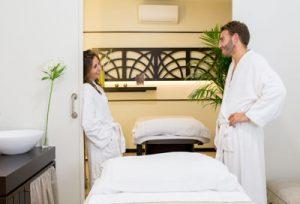 foto de una pareja joven en albornoz, a punto de recibir un masaje en una cabina vip doble. Estan apoyados en la pueda en cada lado de la cabina y se están mirando con expresión de felicidad