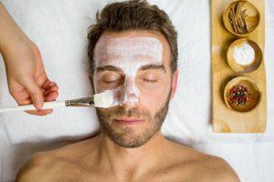 Foto a color de un hombre recibiendo un tratamiento facial. tiene los ojos cerrados y se le esta aplicando la mascarilla con un pincel blanco