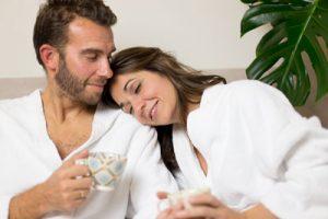 Foto a color de una pareja despues de un tratamiento en Wellness Boutique Experience Madrid. la mujer tiene la cabeza apoyada en la espalda de su marido. Están tomando una taza de té