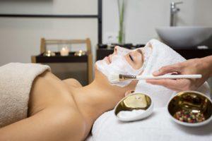 Mujer tumbada en una camilla recibiendo un tratamiento facial. tiene el pelo tapado con una toalla blanca, y se le esta aplicando una mascarilla con un pincel blanco. En primer plano se ven 2 recipientes dorados con productos de cosmetica
