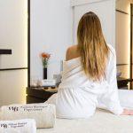 Foto a color de una mujer esperando para su masaje en wellness Boutique Experience. Esta de espalda y lleva puesto un albornoz blanco. Tiene el pelo largo y suelto. En primer plano hay dos toallas bordadas con logo y liadas. La decoración general de la cabina de masaje es moderna y elegante.