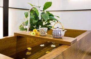 Foto a Color de una Bañera Japonesa de madera, llamada Ofuro. esta llena de agua con flores flotando la la superficie. En el centro se ve una tetera con una tasa de té, y un ramo de margaritas amarillas y naranja, apoyado en la bandeja