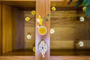 vista desde arriba de una bañera de madera llena de agua con flores flotando. En una tabla aparece una tetera con una taza de té