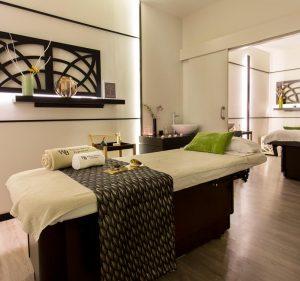 Foto a color de una cabina doble vip en Wellness Boutique Experience Madrid. tienes los tonos generales son oro, gris beige blanco y Marón. Tienen 2 cojines verde
