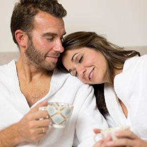 foto a color de una pareja en albornoz tomando el té. Están sentados en un sofa y tiene expresión de felicidad y relajación