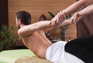 Hombre recibiendo un masaje tailandés. una terapeuta le esta haciendo la postura de la cobra