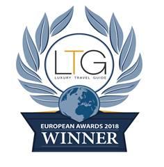 Logo luxury travel guide azul premiando a Wellness Boutique Madrid como mejor Spa de España . en cada lado del premio aparece una corona de laurel azul, y en el centro una planeta tierra de color azul