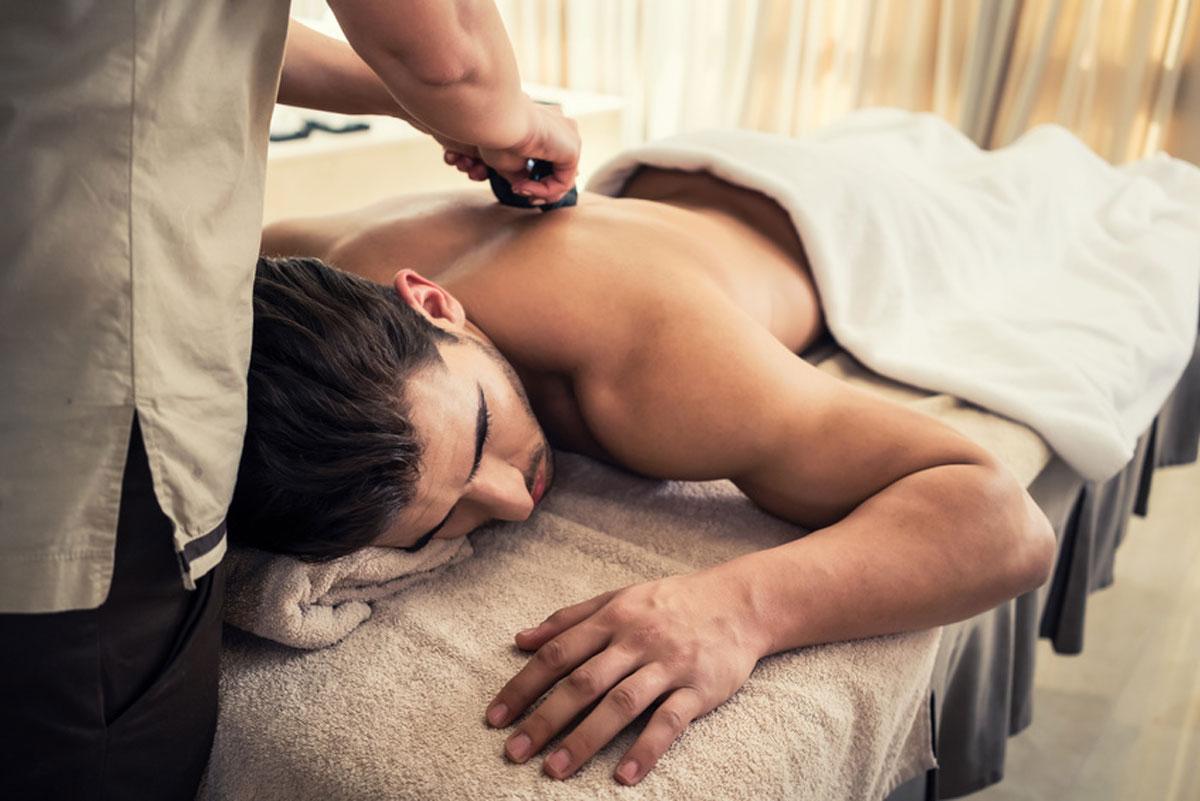 foto a color de un hombre moreno, tumbado en una camilla de masaje. una terapeuta le esta dando un masaje de piedras calientes en la espalda