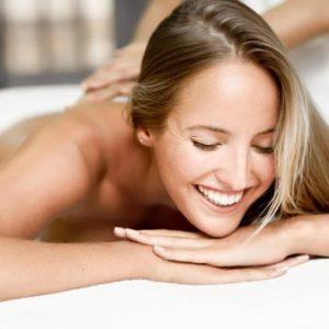 mujer relajada y sonriente a punto de recibir un masaje relajante en Wellness Boutique Experience Madrid. En la parte trasera se ve las manos de una masajista, apoyada en su espalda