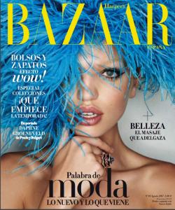 Porta de revista Haper´s Bazaar con logo amaillo. Rostro de una mujer joven con ojos azules. Lleva sobre la cabeza una peluca de plumas azules