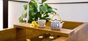 foto a color de una bañera japonesa de madera con flores marillas y naranja, y una tetera hecho a mano