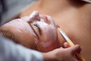 Foto de una mujer disfrutando de un tratamiento facial antiededad en Wellness Boutique Experience madrid. Un esteticista le esta aplicando una mascarilla antiedad sobre el rostro con un pincel marrón.