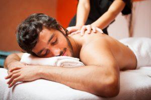 Hombre joven y moreno recibiendo un masaje relajante de espalda. Tiene la espalda descubierta y una masajista le esta apoyando las manos en el centro de la espalda.