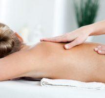 Mujer rubia recibiendo un masaje de espalda tiene el pelo recogido y esta mirando del lado opuesto a la camara. se ven las manos de una masajista deslizando sobre su espalda descubierta