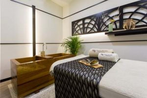 Cabina de masaje y tratamientos faciales. en primer plano se ve parte de una camilla de tratamiento decorado con una tela gris plata, una toallas bordadas con logotipo WB en el fondo esta una bañera de madera japonesa. la decoración es moderna y elegante con un toque minimalista