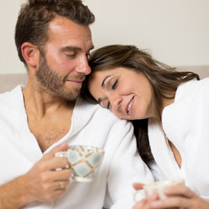 pareja joven, hombre y mujer tomando un té en el sofa de Wellness boutique Experience. Llevan puesto dos albornoces y tiene una tasa de té en las manos. la mujer tiene apoyada su cabeza sobre el hombre de su pareja