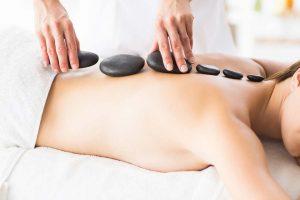 Mujer joven recibiendo un masaje de piedras calientes. Esta tumbada con 6 piedras volcánicas negras en su columna.
