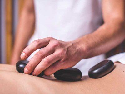 foto a color de un hombre aplicando piedras volcanicas sobre un cuerpo durante un masaje