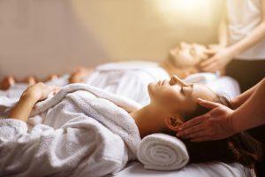 pareja recibiendo un masaje en pareja. estan tumbado boca arriba en una de nuestras cabinas dobles a punto de recibir un masaje relajante llevan puesto un albornoz y están muy relajados. Dos terapeutas tienen tienen puesto sus panos a cada lado de sus cabezas