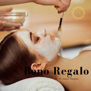 mujer joven con el pelo atado, haciendose un tratamiento facial en centro de estética. Tiene los ojos cerrados y le estan aplicando una mascarilla blanca sobre el rostro