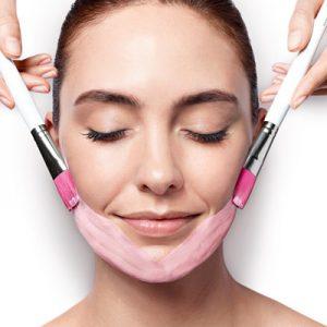 mujer joven morena recibiendo un tratamiento facial antiaging lift experten Wellness Boutique Experience Madrid. lleva el pelo recogido y tiene una media sonrisa. se le esta aplicando con dos pinceles rosa y blanco una mascarilla rosa en zona de mantón.
