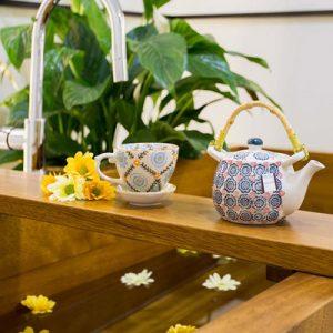 bañera japonesa ofuro de madera . En el centro esta una tetera blanca azul y roja. en el agua aparecen flores flotando.