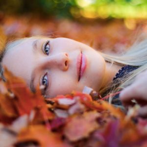 Rostro de una mujer joven tumbada sobre hojas de otoño. Tiene los ojos azules y el pelo rubio. Lleva puesta una camiseta azul