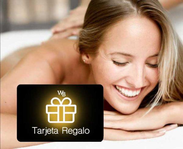 Mujer sonriente tumbada en una camilla de una lujosa cabina de masaje de Wellness Boutique Experience. en primer plano aparece una tarjeta regalo con logotipo WB en Blanco fondo negro y dorado.