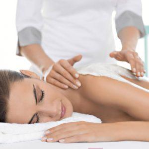 Mujer tumbada en una camilla. Una terapeuta en Wellness Boutique Le esta aplicando una crema de Maria galland para una envolura corporal. la mujer tiene los ojos cerrados y expresión de relajación