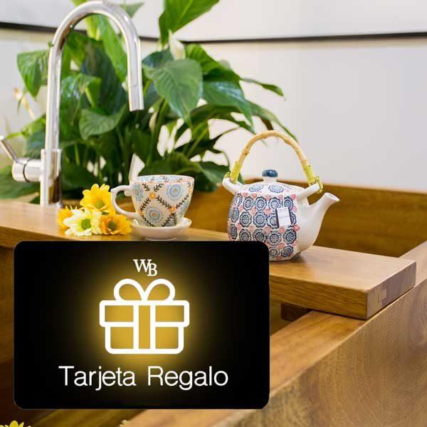 Bañera de madera con una tetera y una tasa apoyados en una mesa central . En primer plano se ve una tarjeta regalo de Wellness Boutique Experience Madrid con fondo negro, logo tipo blanco y el centro de color oro