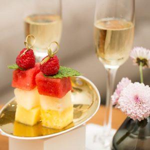 Brocheta de fruta elegante y moderna, con frambuesa, melón, menta, sandía y piña. En el fondo aparecen 2 copas de cava y a la derecha 3 flores rosas