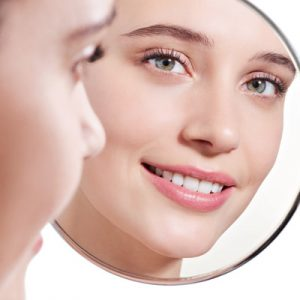 Rostro de una mujer joven mirándose en el espejo depués de un tratamiento facial