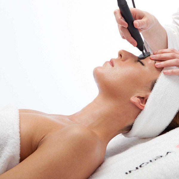Mujer joven tumbada en una camilla, recibiendo un tratamiento facial con la aparatologia de radiofrecuencia Indiba Deep Beauty. le estan aplicando el manipulo en la frente, tiene los ojos cerrados y esta muy relajada