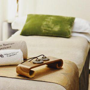 Camilla de masaje con decoración elegante en Wellness Boutique Experience Madrid. En el primer plano se ve unos platillos de meditación Tibetano. En el fondo de la foto se ve un cojín verde