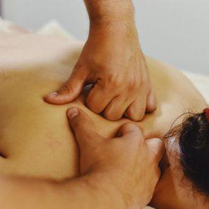 Mujer tumbada en una camilla con las mano de un terapeuta haciendo un masaje profundo de espalda en zona trapecio, romboidés