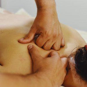 Mujer recibiendo un quiromasaje en zona alta de espalda. Se ven las mano del terapeuta realizando unas maniobras descontracturantes