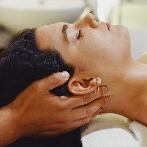 Mujer tumbada en una camilla con los ojos cerrados, se ven las manos del terapeuta apoyando por detrás su cabeza en zona occipital