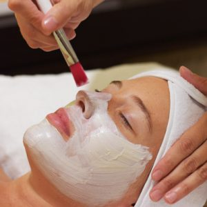 Rostro de una mujer joven tumbada en un camilla. Aparecen las manos de la terapeuta con un pincel, aplicando una mascarilla de arcilla .