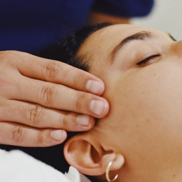 Una mujer esta recibiendo una masaje de cabeza. el terapeuta tiene sus dedos apoyados en cada lado de su cabeza