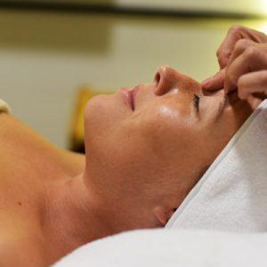 foto a color de una mujer tumbada en una camilla. Solo se ve su rostro, en su frente tiene apoyado los dedos de una terapeuta. lleva una toalla blanca alrededor del pelo