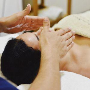 Mujer recibiendo una tratamiento y masaje de aromaterapia . Esta tumbada en una camilla y un terapeuta tiene la manos abiertas, y sostenidas encima de su nariz
