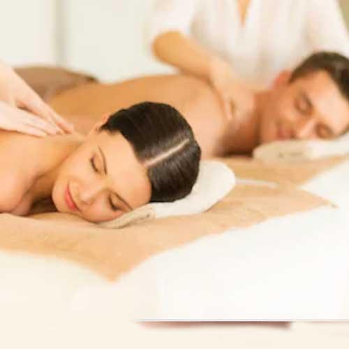 Pareja recibiendo un masaje doble una cabina doble de Wellness Boutique Experience Madrid. se ve una pareja tumbados con los ojos cerrados. dos terapeutas les están dando un masaje de espalda
