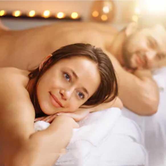 Hombre y mujer tumbados en dos camillas a punto de recibir un masaje en Wellness Boutique Experience Madrid. Ambos tienen media sonrisa y parecen muy relajados