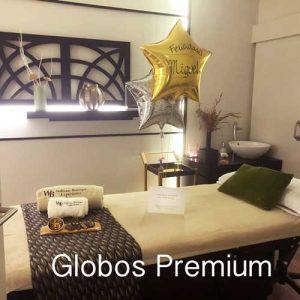 Foto de una cabina en Wellness boutique Experience Madrid con unos globos de helio color oro y plata, apoyados encima de la camilla de masaje para un regalo original