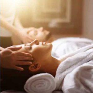 Pareja hombre y mujer tumbados en 2 camillas juntas, a punto de disfrutar de un Ritual en Wellness Boutique Experience Madrid. llevan 2 albornoces y las terapeutas tienen las manos apoyadas en cada lado de su cabeza, justo antes de recibir un masaje