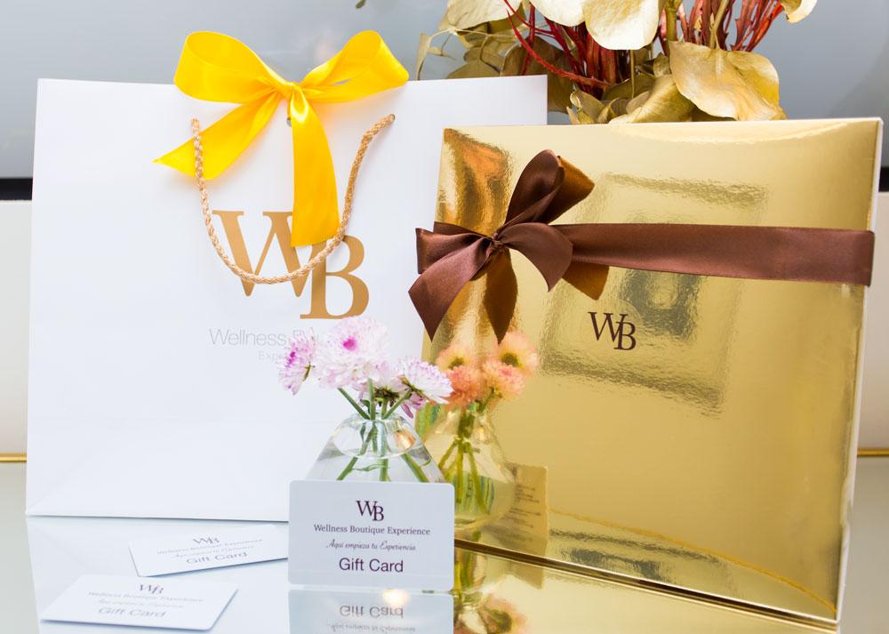 foto a color de los bonos regalos en wellness Boutique experience madrid. En primer plano, viene una tarjeta con logotipo apoyada sobre un pequeño florero con 4 flores rosa. A la derecha se ve una caja de regalo dorada con un lazo marrón. En el lado izquierdo aparece una bolsa blanca con logotipo de Wellness Boutique Experience dorado, y un lazo amarillo