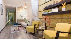 zona de espera en Wellness Boutique Experience con 2 sillones amarillos, un sofa gris . diseño moderno y elegante